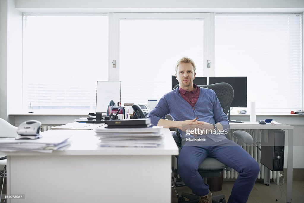 Confident businessman sitting his office : Stock Photo