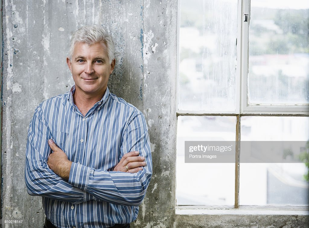 Confident businessman standing against wall