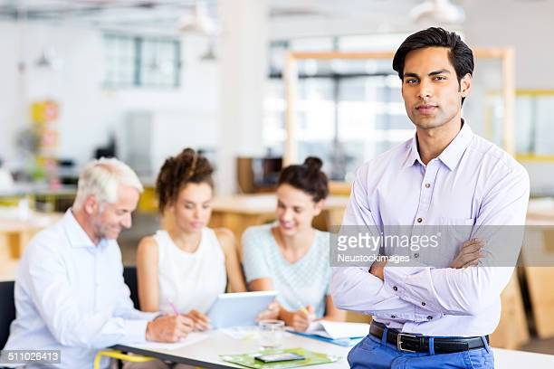 Confident Businessman Standing Arms Crossed At Office
