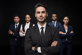 Confident businessman standing with group of business colleagues behind isolated on black