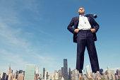Confident Businessman Towers Over City Skyline