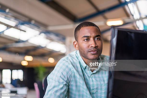 Confident businessman using computer in office
