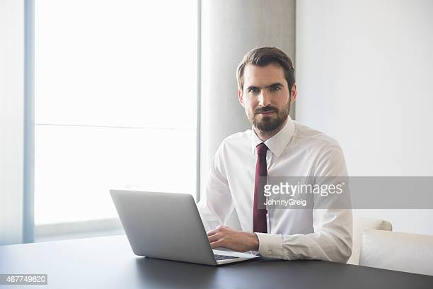 Confident Businessman Using Laptop At Conference Table