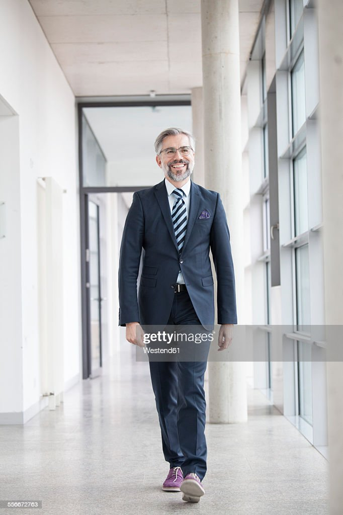 Confident businessman walking on hallway