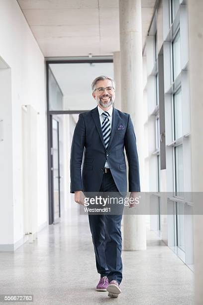 Confident businessman walking on hallway
