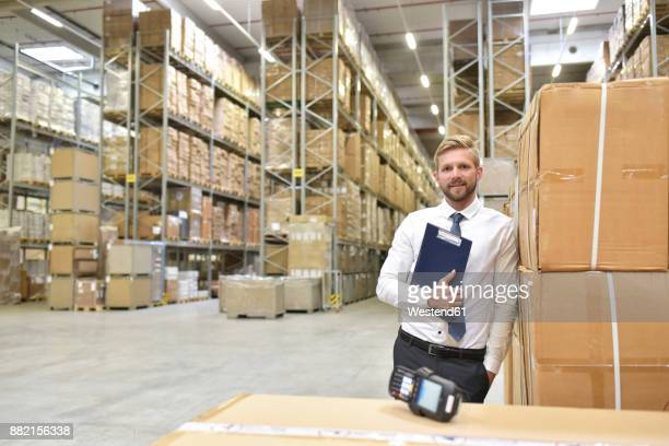 Confident businessman with clipboard and barcode scanner in warehouse
