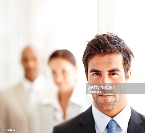 Confident businessman with colleagues in background