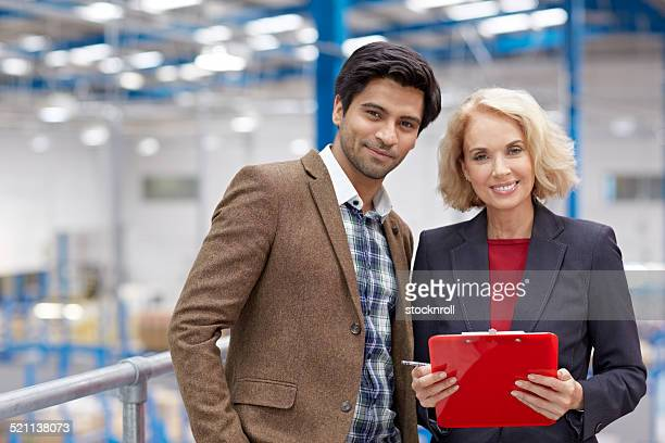 Confident businessman with senior female colleague in factory
