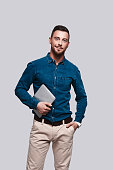 Good looking young man in smart casual wear looking at camera and smiling while standing against grey background