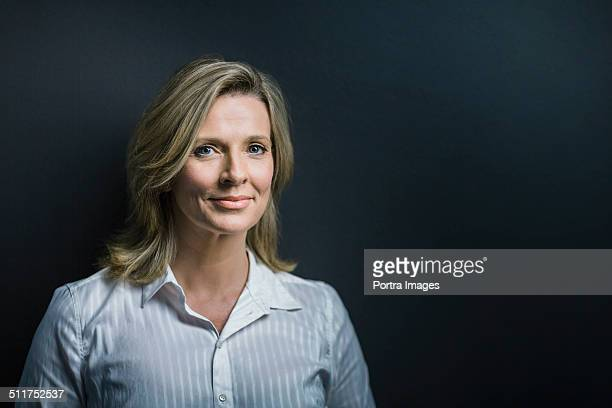Confident businesswoman against blue background