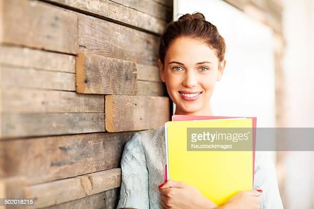 Confiant Femme d'affaires tenant des fichiers tout en s'appuyant sur le mur de