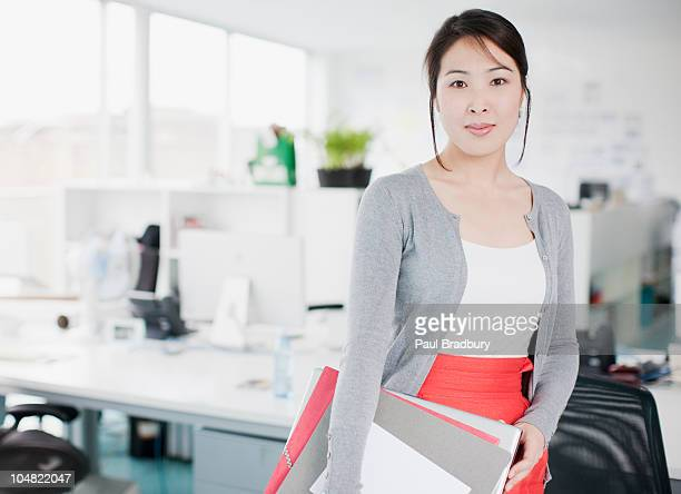 Confident businesswoman holding folders in office