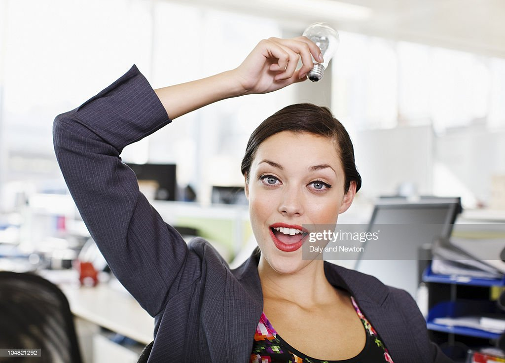 Confident businesswoman holding light bulb overhead in office