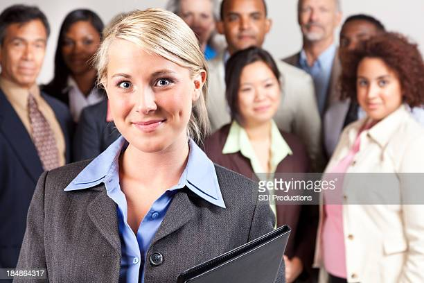 Confident businesswoman in front of diverse business team