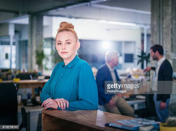 Confident businesswoman leaning on desk in office