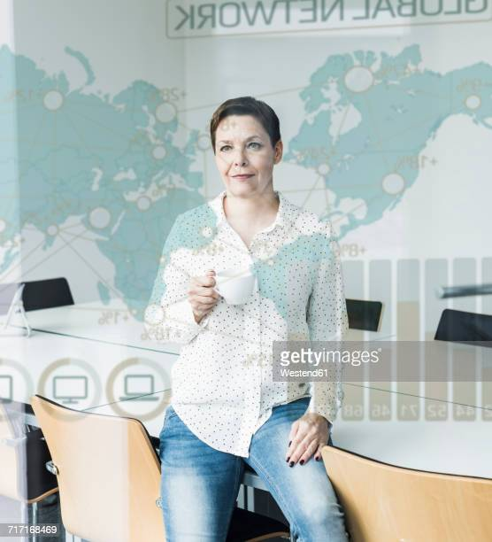 Confident businesswoman looking at glass pane with world map and global network in office