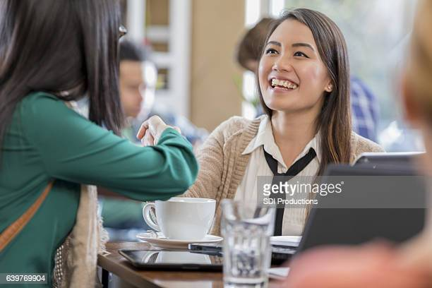 Confident businesswoman shakes colleagues hand in coffee shop