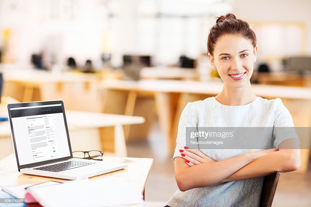 Confident Businesswoman Sitting Arms Crossed At Desk : Stock Photo