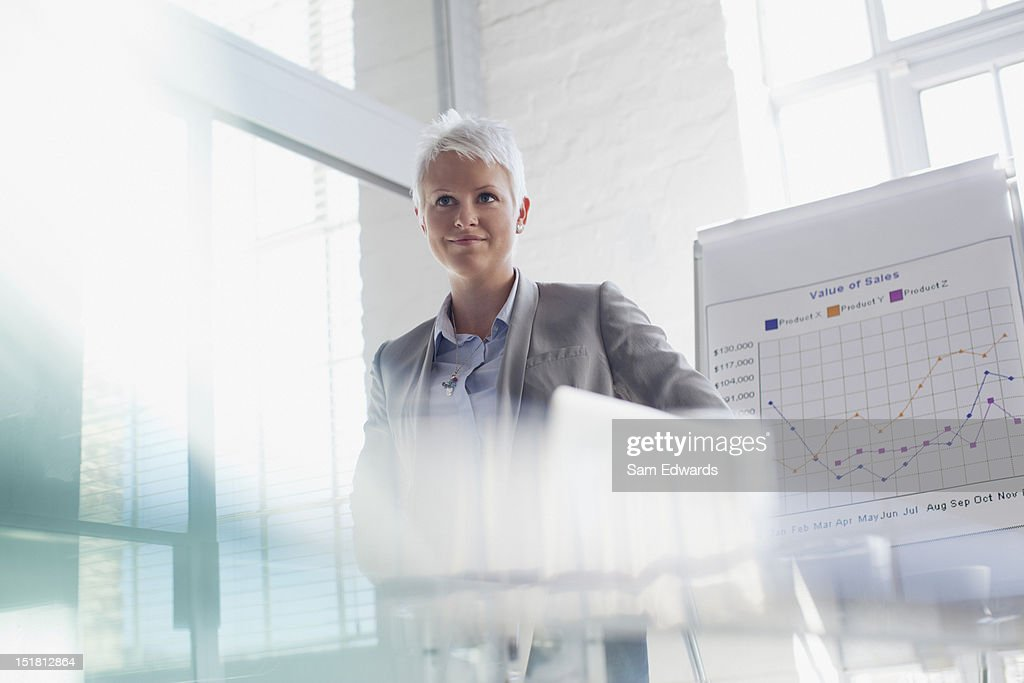 Confident businesswoman standing next to chart in conference room : Stock Photo