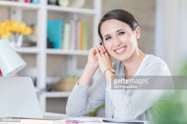 Confident businesswoman telecommutes from her home office