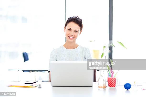 Zuversichtlich Geschäftsfrau mit Laptop am Schreibtisch im Büro