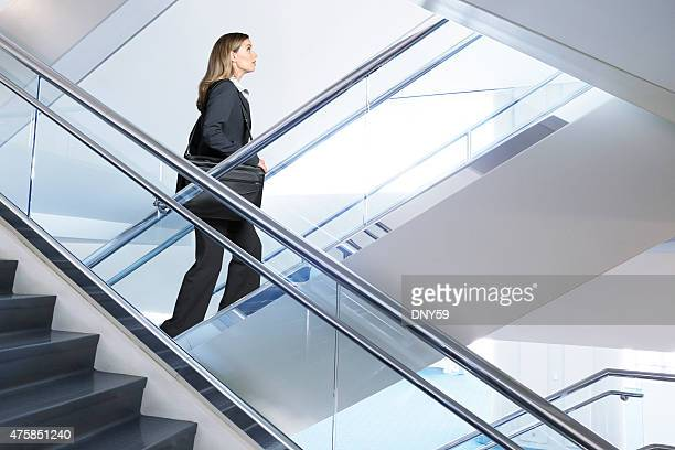 Confident businesswoman walking up flight of stairs