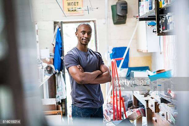 Confident carpenter standing with arms crossed in workshop