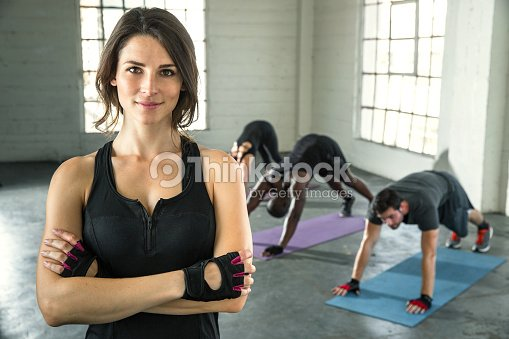 Confident cheerful beautiful physical fitness exercise trainer smiling successful : Stock Photo