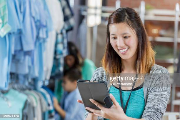 Confident clothing store manager uses tablet to check inventory