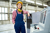 Smiling beautiful young intern working in factory and knowing how to manage CNC machine looking at camera confidently