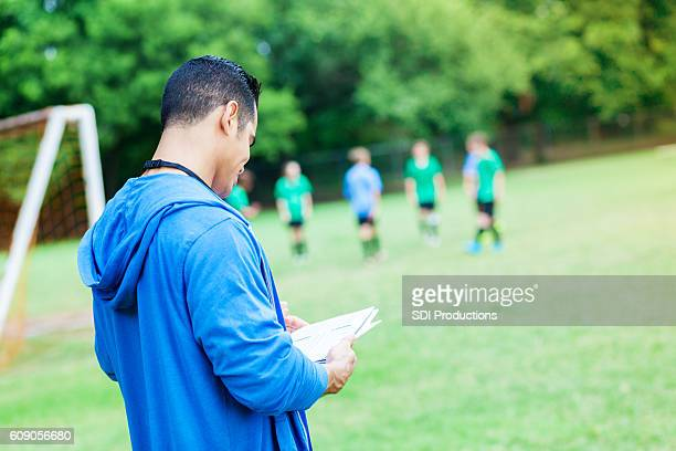 Confident coach reviews plays during soccer game
