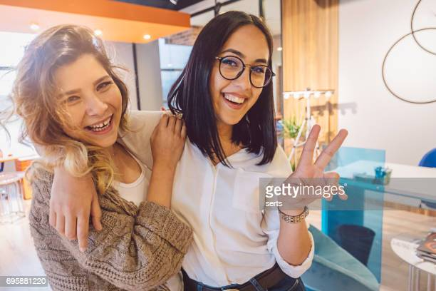 Confident colleagues businesswomen having fun in office