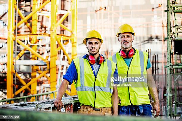 Confident construction workers standing at site