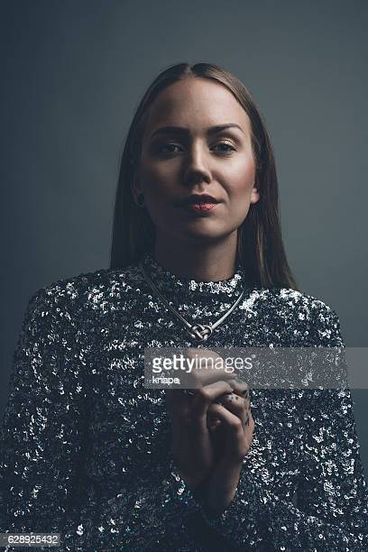 Confident cool real woman studio portrait in party dress