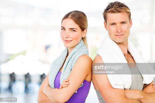 Confident Couple With Towels Standing Arms Crossed In Gym