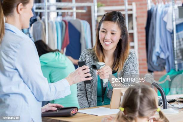 Confident department store employee scans customer's smart phone