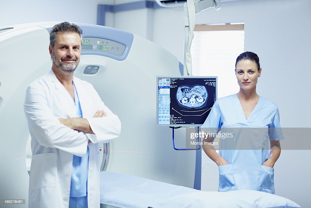 Confident doctor and nurse by CT scanner