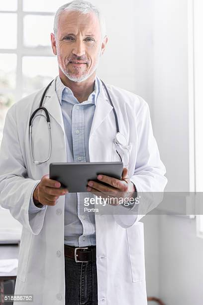 Confident doctor holding digital tablet in clinic