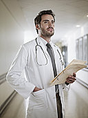 Confident doctor holding medical record in hospital corridor