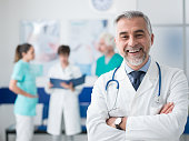 Confident smiling doctor posing and the hospital with arms crossed and medical team working on the background