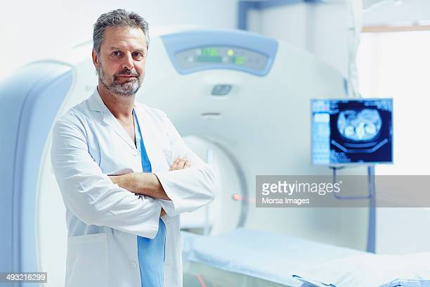 Confident doctor standing by CT scanner