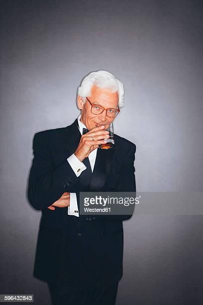 Confident elegant senior man drinking from tumbler