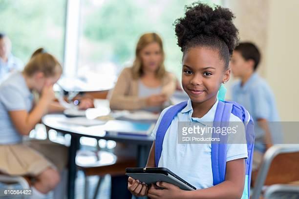 Confident  elementary schoolgirl in classroom