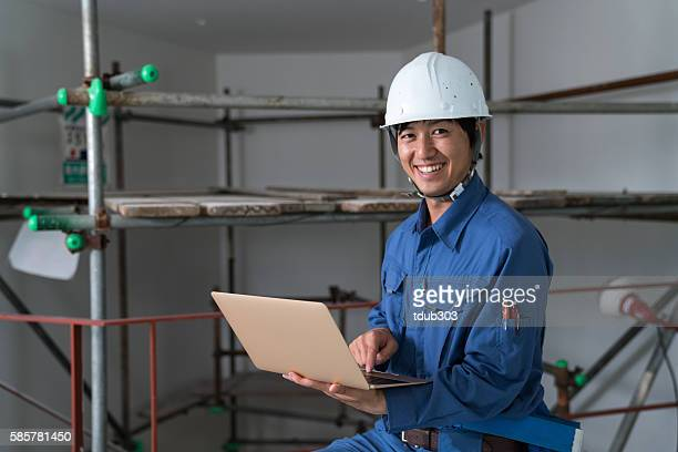 Confident engineer at a construction project holding a laptop computer