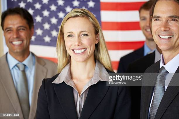 Confident executives smiling in front of flag