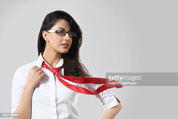 Confident fashionable businesswoman with windswept tie over gray background