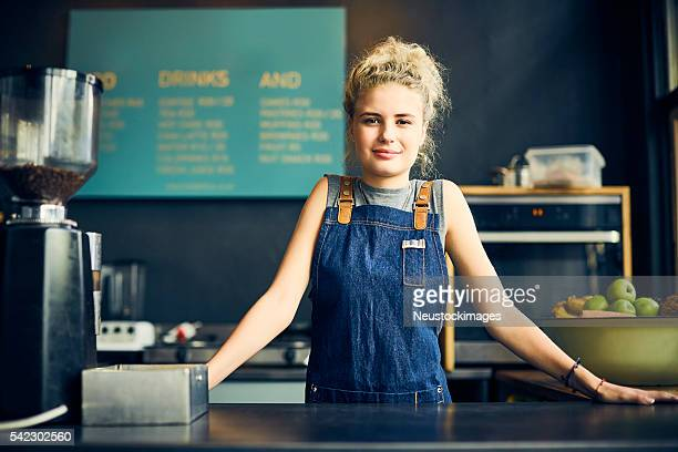 Confident female barista leaning on cafe counter