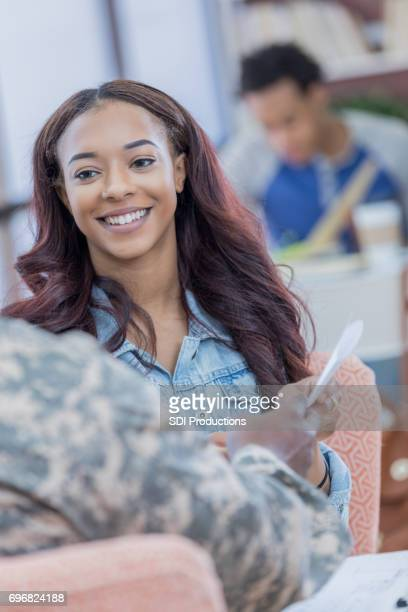 Confident female college student talks with army recruiter
