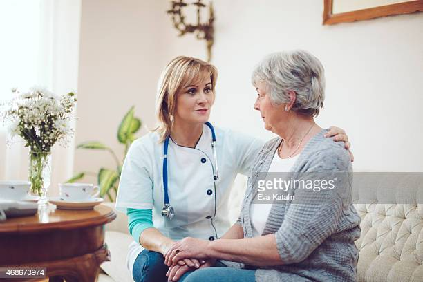 Confident female doctor examines her senior patient