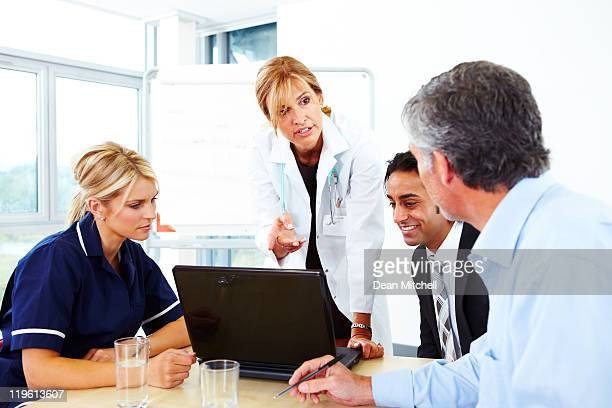 Confident female doctor showing laptop to colleagues